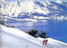 Lake Tahoe skiers enjoy the view of Lake Tahoe in the background framed by the snow covered mountains.